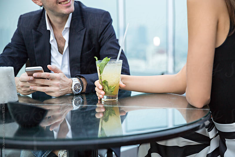 Closeup of a woman holding her cocktail glass on a date in a modern restaurant  by Jovo Jovanovic for Stocksy United