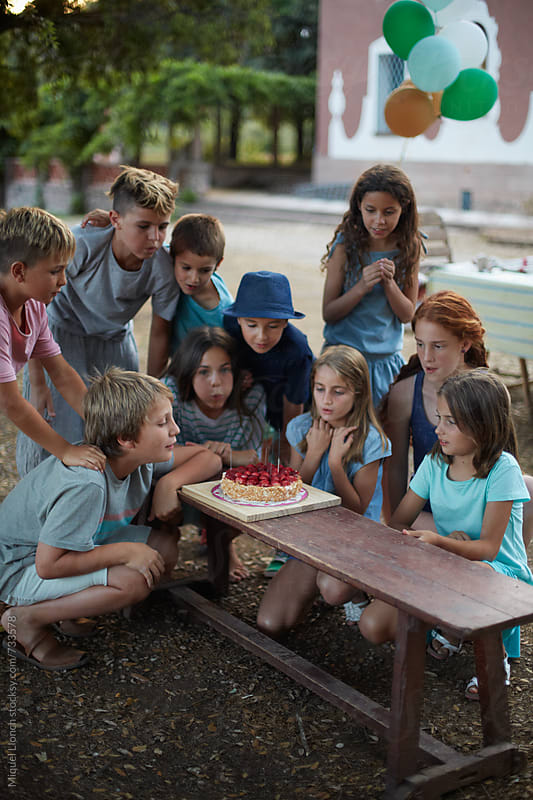 Group of ten children celebrating a birthday with cake by Miquel Llonch for Stocksy United