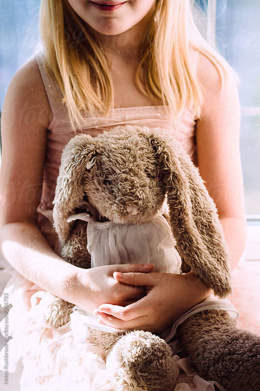 A little girl and a toy rabbit. by Helen Rushbrook for Stocksy United