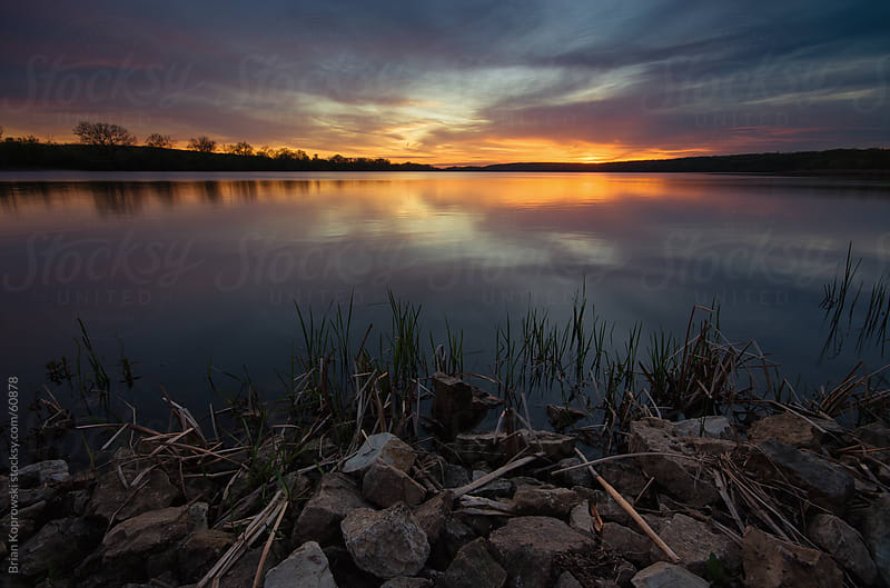 Sunset at a Lake Reflecting by Brian Koprowski for Stocksy United