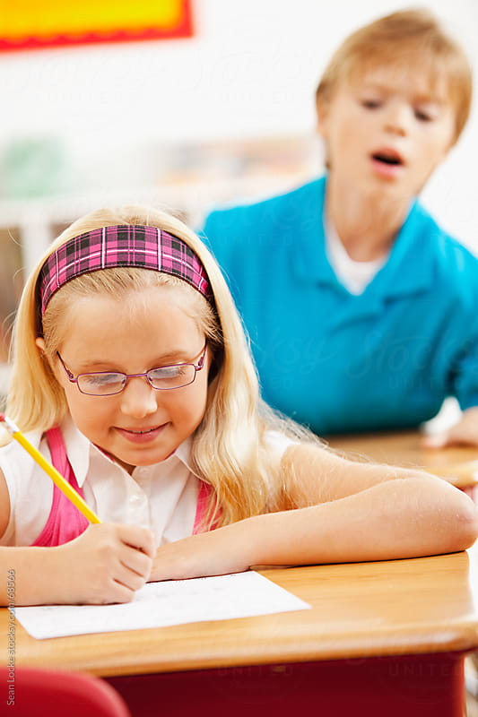Classroom: Boy Tries to Peek at Girl's Answers by Sean Locke for Stocksy United