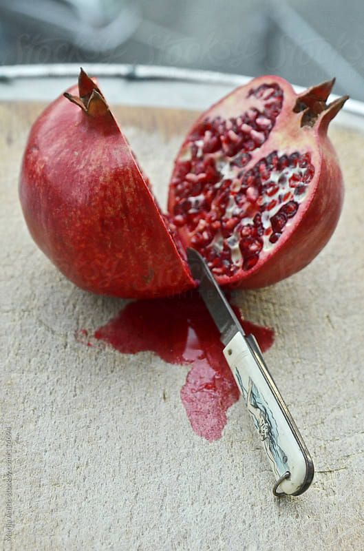 sliced pomegranate on plate by Marija Anicic for Stocksy United