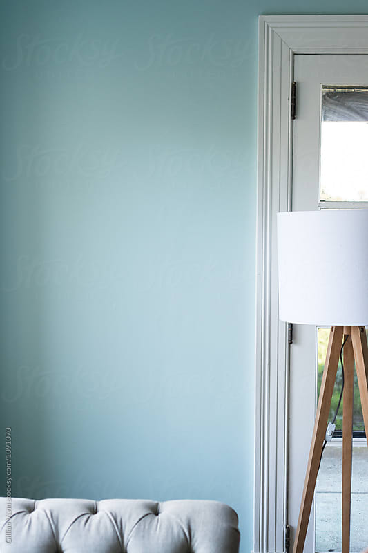 corner of a living room, with lamp and blue wall with empty space by Gillian Vann for Stocksy United