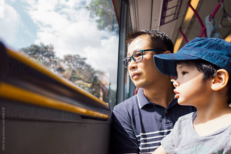 Dad and young son in a bus by Alita Ong for Stocksy United