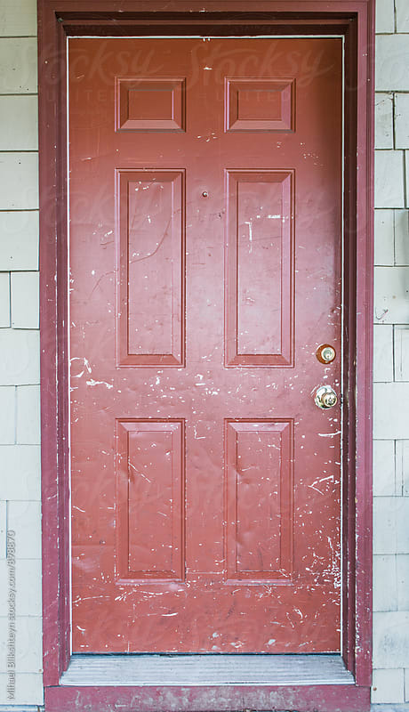 Scratched old red house door of a white house by Mihael Blikshteyn for Stocksy United