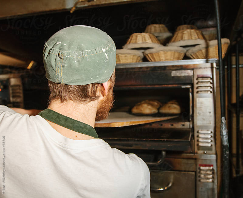 Baker pulling out freshly baked bread at a commercial artisinal bakery by Mihael Blikshteyn for Stocksy United
