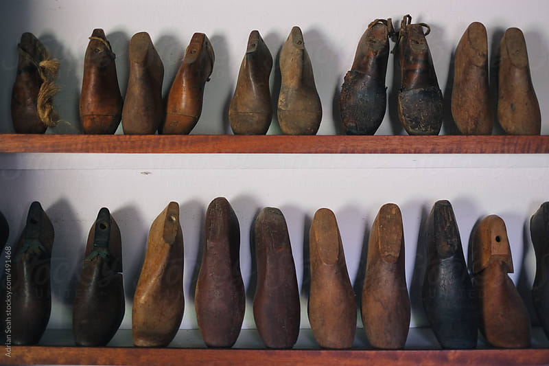 Antique wooden shoe fillers line the shelves by Adrian Seah for Stocksy United
