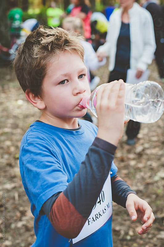 Exhausted boy quenches his thirst using a water bottle after a sport competition. by Lea Csontos for Stocksy United