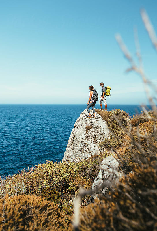 two hikers standing on a rocky outcrop overlooking the sea in Kalymnos, Greece by Micky Wiswedel for Stocksy United