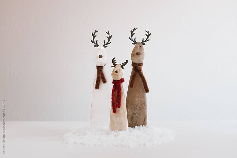 Reindeer family Christmas decorations sitting in snow by Darren Seamark for Stocksy United