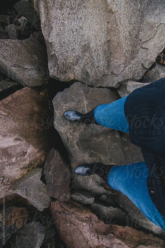 woman's legs and feet climbing on rocks by Margaret Vincent for Stocksy United