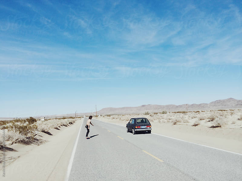 Man Skateboarding by Car by Kevin Russ for Stocksy United