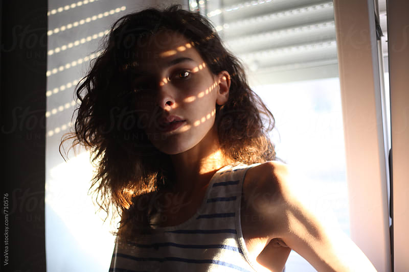 Portrait of a woman standing near a window with light spots on her face by VeaVea for Stocksy United