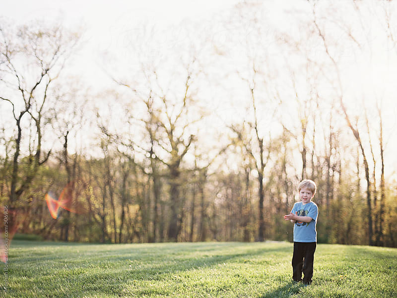 Young boy playing in the yard in late spring sun by Meghan Boyer for Stocksy United