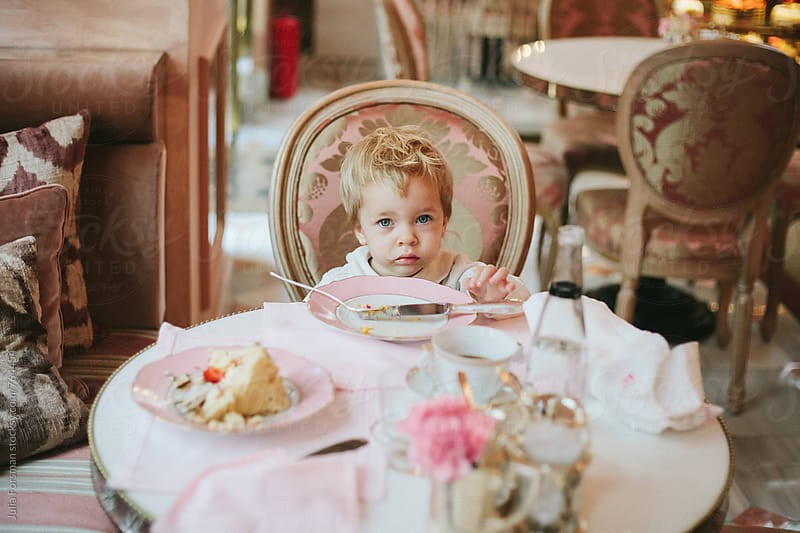 A little girl sits at a beautifully laid table eating cake in a pretty old-fashioned patisserie. by Julia Forsman for Stocksy United