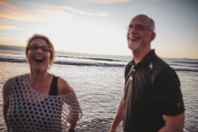 Happy middle aged, retired couple laughing together outside on ocean beach by Rob and Julia Campbell for Stocksy United