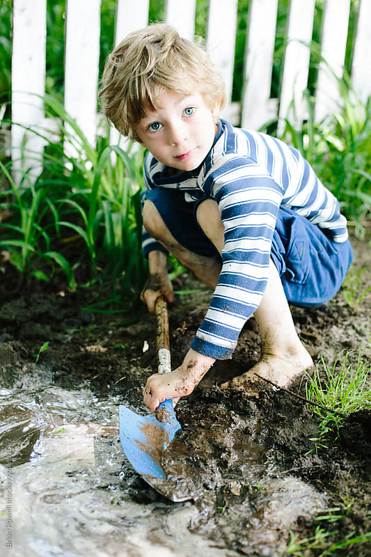 boy playing in the mud with shovel by Brian Powell for Stocksy United