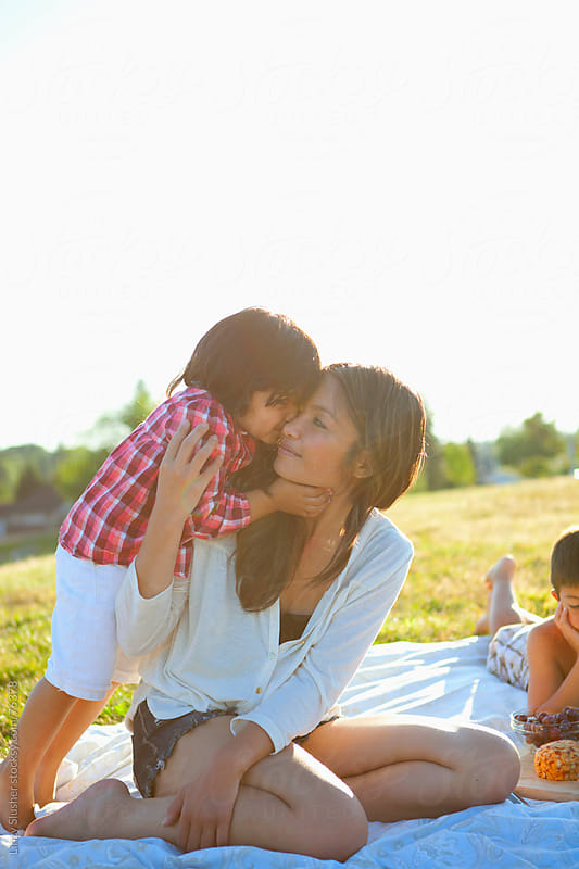 Mother hugs daughter at family summer picnic by Linzy Slusher for Stocksy United