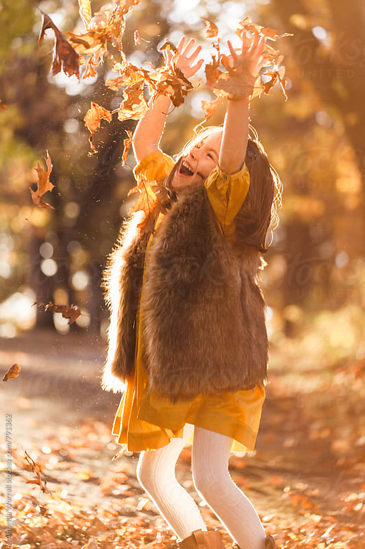 A joyful girl playing in the fall leaves, arms in air by Amanda Worrall for Stocksy United