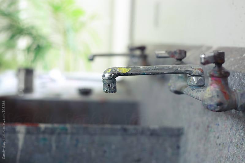 Metal, paint splattered sink in an artist's studio by Carolyn Lagattuta for Stocksy United