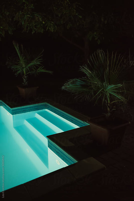 View of an outdoor pool at night by Lea Csontos for Stocksy United