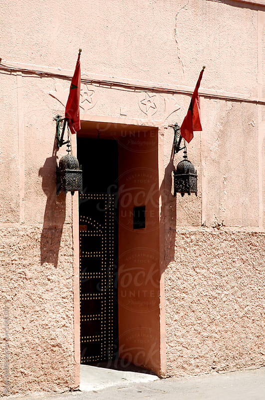 Door in the medina in Marrakech with lamps and flags of Morocco by Bisual Studio for Stocksy United