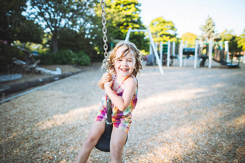 Young girl on zip-line swing in summer by Rob and Julia Campbell for Stocksy United