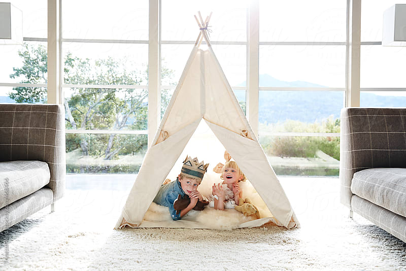 Brother and sister playing in teepee tent in living room by Trinette Reed for Stocksy United