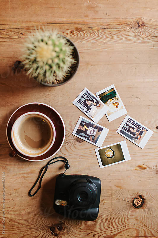 An instant camera and film laying on a coffee table by Kristen Curette Hines for Stocksy United