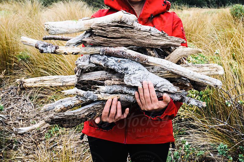 Woman carrying firewood, The Douglas Range, Kahurangi National Park, New Zealand. by Thomas Pickard for Stocksy United