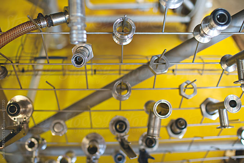 close up of collection of valves and spare parts from brewing beer machinery by Natalie JEFFCOTT for Stocksy United