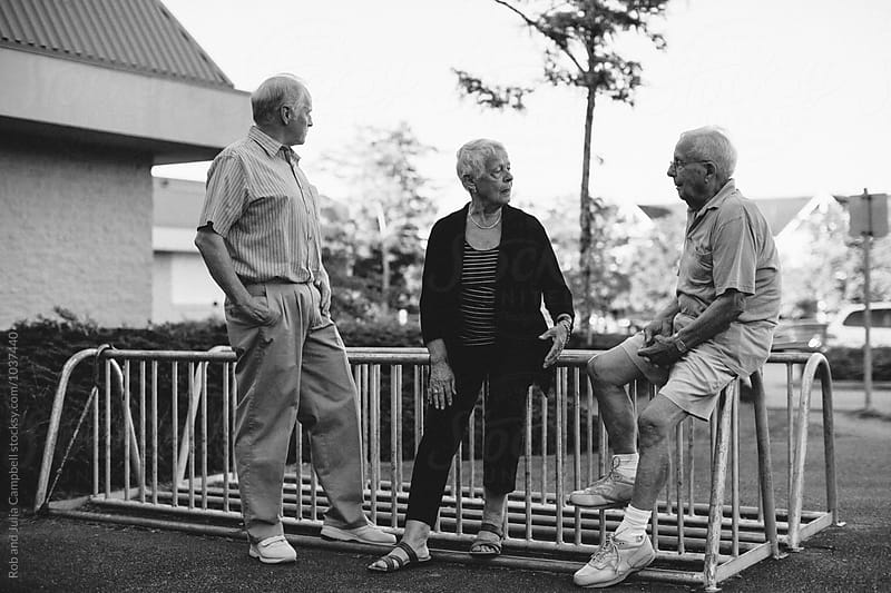 Fun portrait of happy caucasian seniors outside at schoolyard bike racks by Rob and Julia Campbell for Stocksy United
