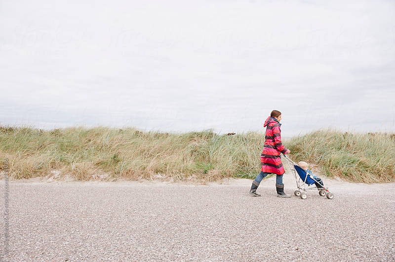 Mother with son in push chair infront of dune at the Baltic Sea by Urs Siedentop & Co for Stocksy United