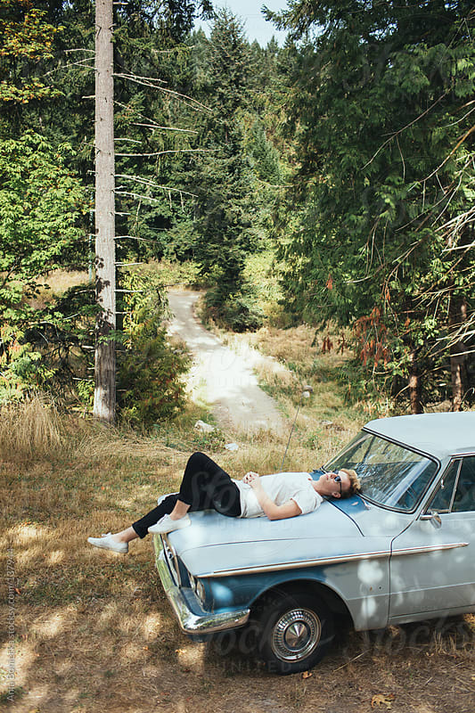 A teenager lying on the hood of his blue car by Ania Boniecka for Stocksy United