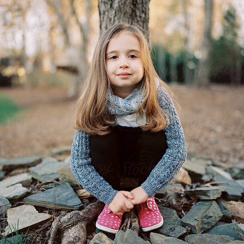Portrait of a beautiful young girl with a scarf sitting by a tree by Jakob for Stocksy United