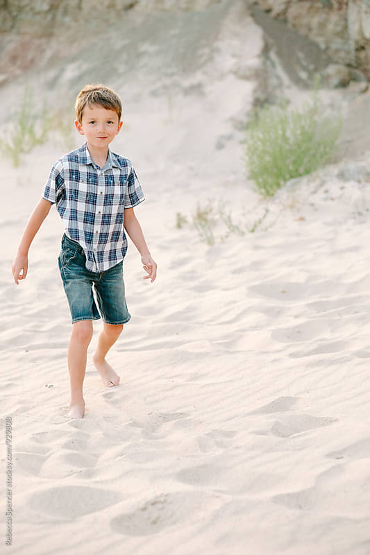 Young boy on a beach in shorts about to cause mischief by Rebecca Spencer for Stocksy United