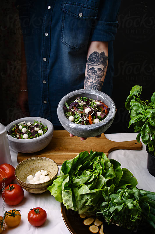 Woman preparing salad. Woman with tattoo's giving salad bowl for dinner. by Darren Muir for Stocksy United