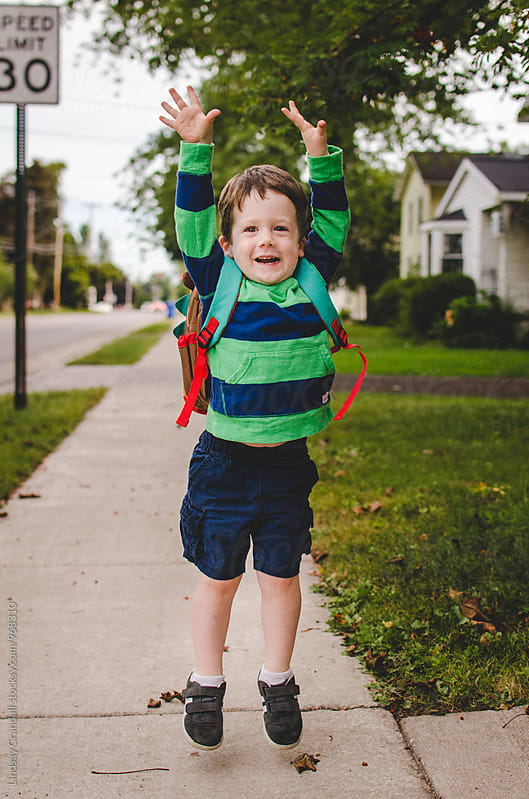 Happy young boy wearing a backpack and jumping by Lindsay Crandall for Stocksy United