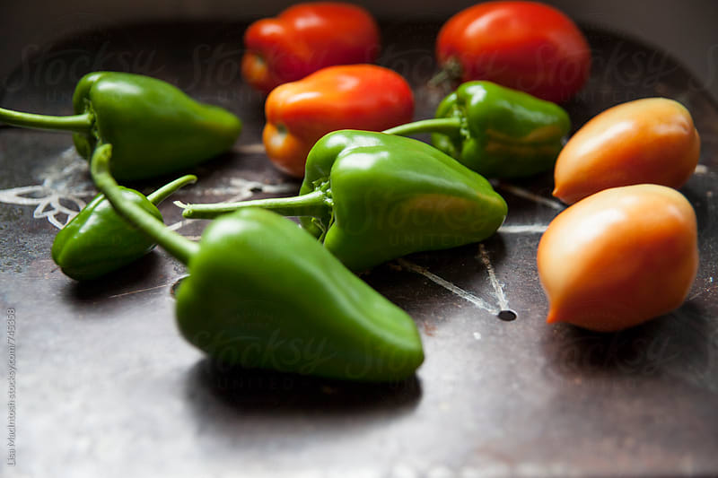 garden fresh green peppers and tomatoes by Lisa MacIntosh for Stocksy United