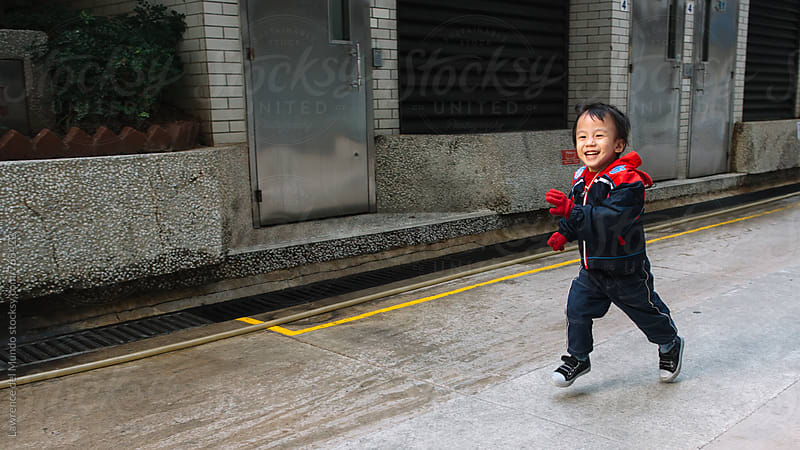 A young kid wearing cold weather clothes running happily in an alley  by Lawrence del Mundo for Stocksy United