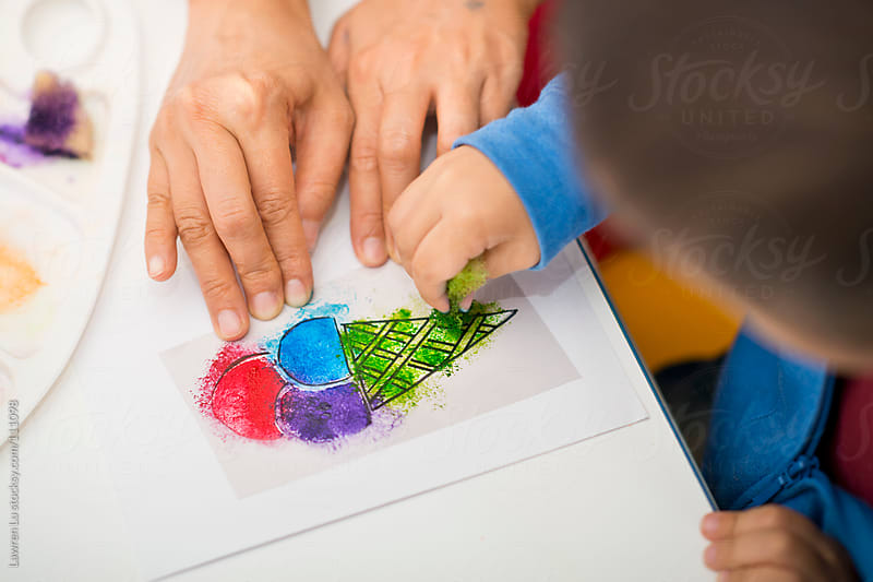 Child learns to paint, mother assistants son to paint by Lawren Lu for Stocksy United