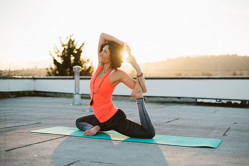 Young woman in a seated yoga twist on rooftop at sunset. by Kate Daigneault for Stocksy United
