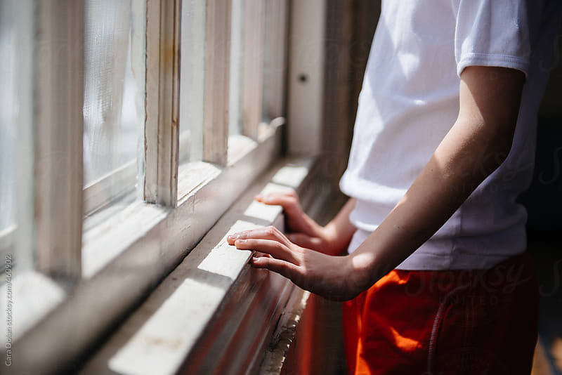 Child's hands rest on sunny windowsill by Cara Dolan for Stocksy United