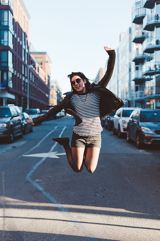 Happy young woman jumping in New York by Good Vibrations Images for Stocksy United