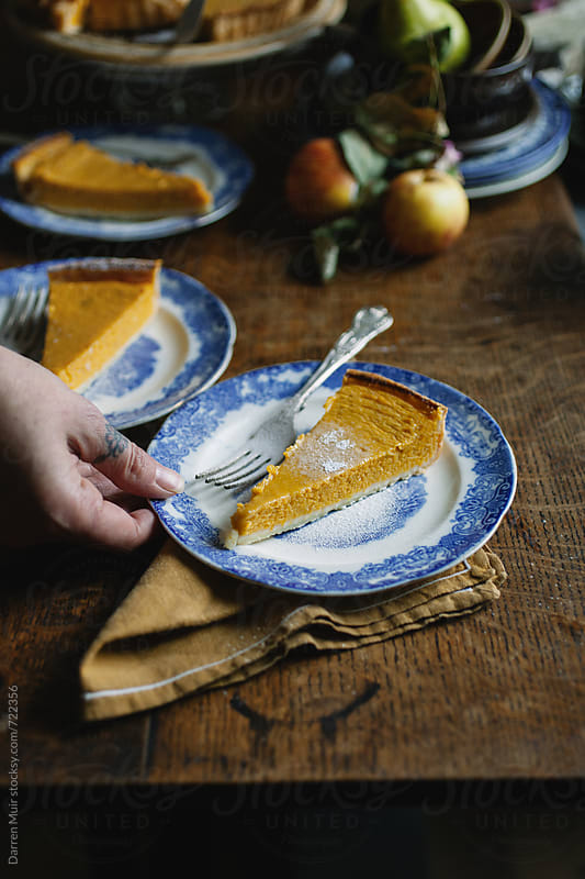 Woman's hand reaching for a plate of pumpkin pie from the table. by Darren Muir for Stocksy United
