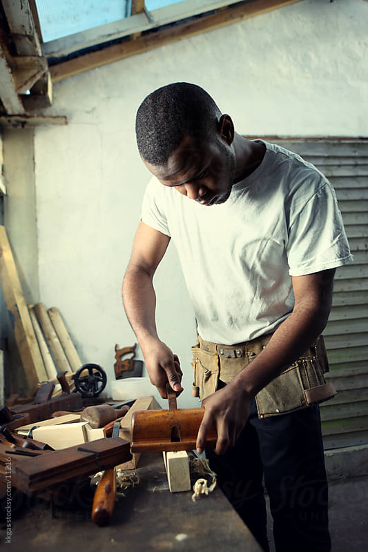 Carpenter working with a piece of wood. by kkgas for Stocksy United
