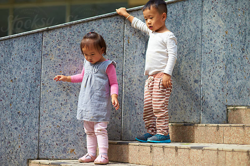 two little asian kids outdoor on stairs by Bo Bo for Stocksy United