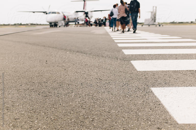 People walking towards a Plane to Board by Gary Radler Photography for Stocksy United