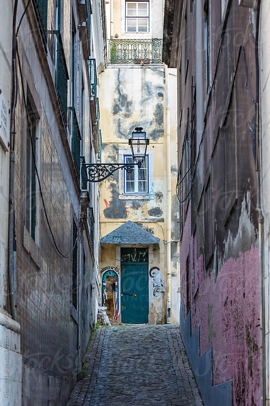 View up a very narrow cobblestone street in Lisbon, Portugal by Amanda Large for Stocksy United