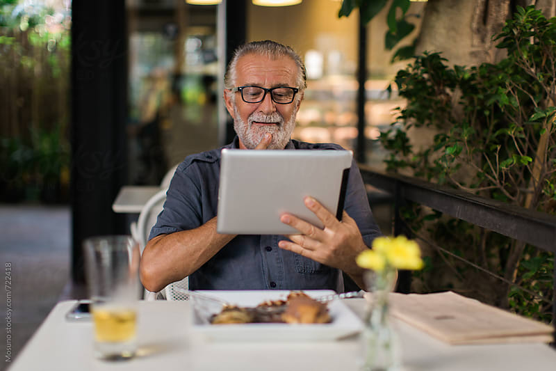 Senior Man Using Technology in a Restaurant by Mosuno for Stocksy United